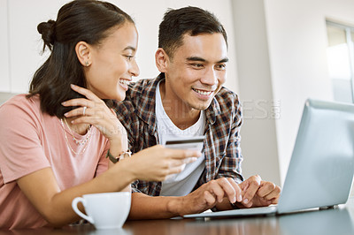 Buy stock photo Shot of a young couple buying items online at home