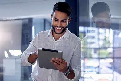 Buy stock photo Shot of a young businessman using his digital tablet at work