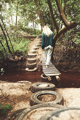 Buy stock photo Shot of a woman crossing a footbridge while exploring nature