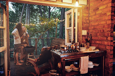 Buy stock photo Shot of a young couple preparing dinner while on vacation in a cabin