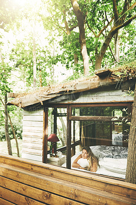 Buy stock photo Shot of a young woman looking out the window while lying on a bed in a cabin