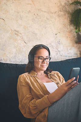 Buy stock photo Shot of a young woman using headphones and a smartphone while relaxing on the sofa at home
