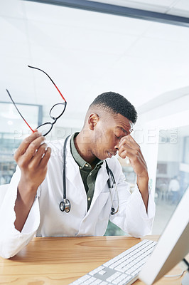 Buy stock photo Shot of a handsome young doctor sitting alone in his office at the clinic and feeling stressed using his computer