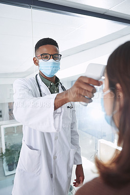 Buy stock photo Shot of a young doctor wearing a mask and standing with a patient in the clinic while taking her temperature