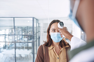 Buy stock photo Shot of a young woman wearing a mask and getting her temperature checked by her doctor in the clinic