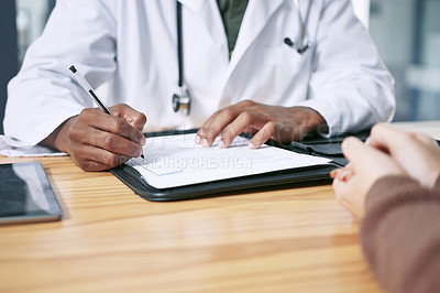 Buy stock photo Cropped shot of an unrecognizable doctor sitting with his patient and writing a prescription during a consultation in the clinic