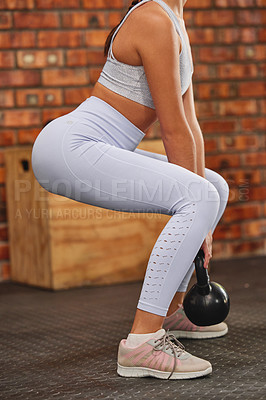 Buy stock photo Cropped shot of an unrecognizable woman squatting and using a kettle bell at the gym