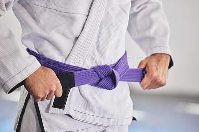 Buy stock photo Cropped shot of an unrecognizable man tying a purple belt around hist waist while in full jiu jitsu gi