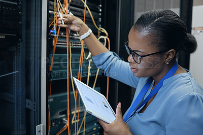 Buy stock photo Cropped shot of an attractive female programmer working on a tablet in a server room