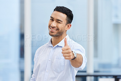 Buy stock photo Shot of a handsome young businessman standing alone in the office and making a thumbs up gesture