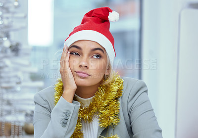 Buy stock photo Shot of a sad young woman lost in thought at her desk in the office