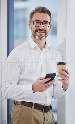 Buy stock photo Shot of a businessman using his smartphone while drinking coffee