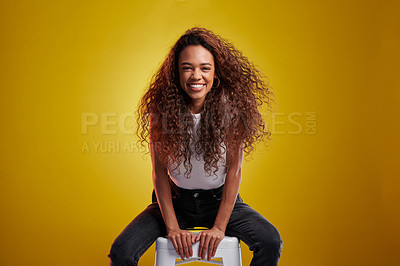 Buy stock photo Studio portrait of a young woman sitting on a chair against a yellow background