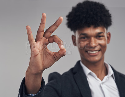 Buy stock photo Studio shot of a young businessman showing an okay hand gesture against a grey background