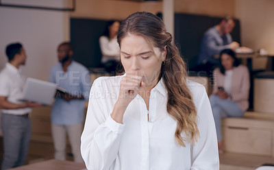 Buy stock photo Shot of an attractive young businesswoman standing in the office and coughing