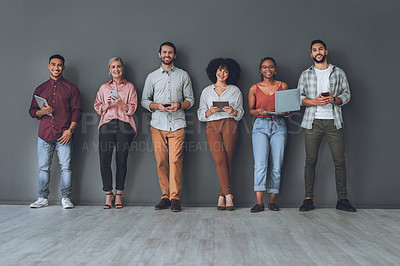 Buy stock photo Studio portrait of a diverse group of people using digital devices against a grey background