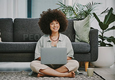 Buy stock photo Full length shot of an attractive young woman sitting on the floor in her living room and using her laptop