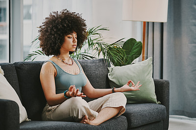 Buy stock photo Full length shot of an attractive young woman sitting alone on her sofa at home and meditating