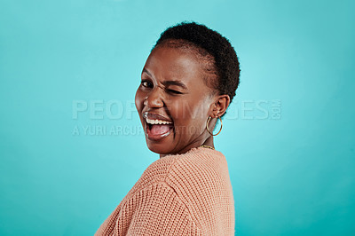 Buy stock photo Shot of a beautiful young woman winking while standing against a turquoise background