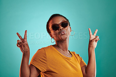 Buy stock photo Shot of a woman wearing sunglasses and showing the peace sign while standing against a turquoise background
