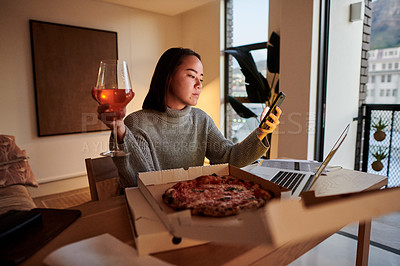 Buy stock photo Shot of a young woman taking a break from working to have pizza and wine while using her smartphone
