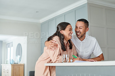 Buy stock photo Shot of a young couple sitting together and laughing during a day at home