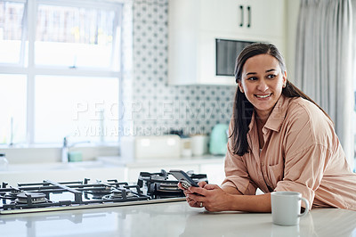 Buy stock photo Shot of an attractive young woman leaning on her kitchen counter at home and using her cellphone