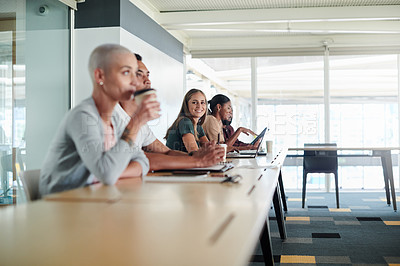 Buy stock photo Cropped shot of a group of young businesspeople sitting in the boardroom during a seminar