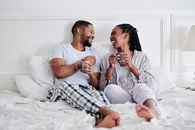 Buy stock photo Full length shot of a young couple sitting in bed together and enjoying a cup of coffee in the morning