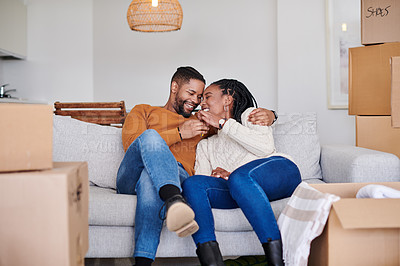 Buy stock photo Shot of a young couple holding the keys to their new house while sitting on the couch