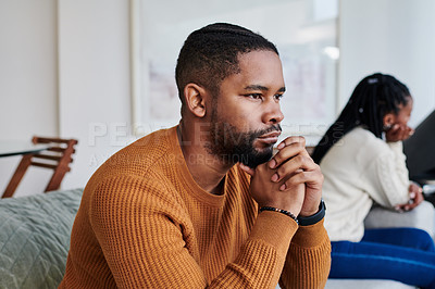 Buy stock photo Shot of a young man looking upset after an argument with his partner at home