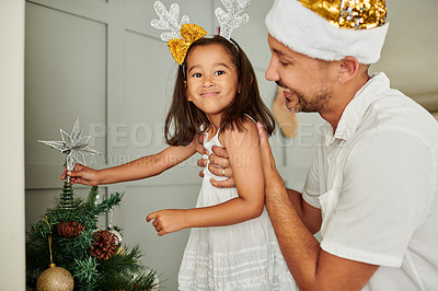 Buy stock photo Cropped portrait of an adorable little girl putting the star on top of her family Christmas with a little help from dad